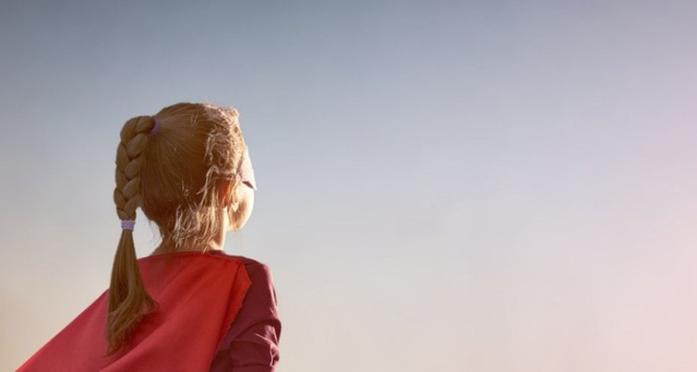 An animated child with hair tied back in a plait wearing a red cape and their back to the viewer as they look into the sun