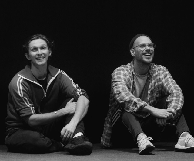 Black and White Photo - two men sit on the floor side by side smiling