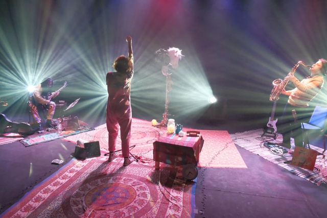 Taken from the back of the stage, floors are carpeted, stage lights beams are splayed out, an actor stands with their back to us in between a saxophonist and a guitarist